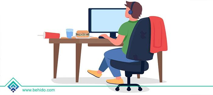مردی پشت کامپیوتر در اتاق نشسته است